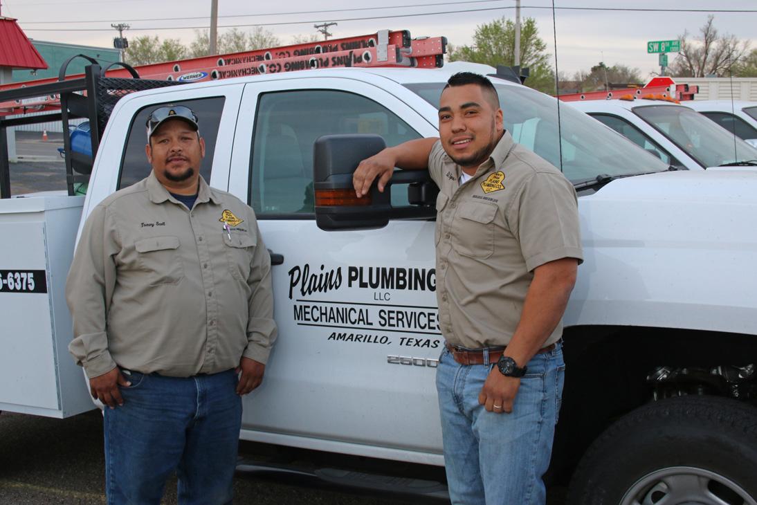 Service Plumbing guys standing in front of truck